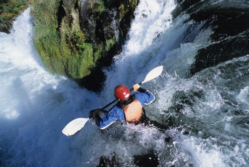 kayaker in waterfall